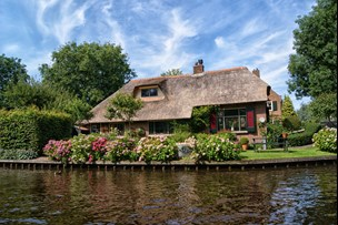 Thatched roof cottage by the canal