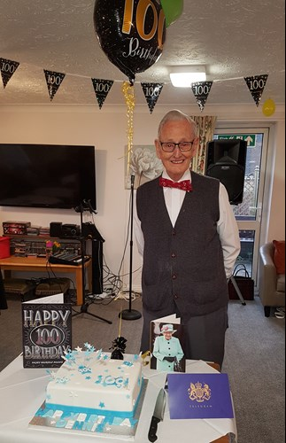 Dennis Busby with his balloons and cake on his 100th birthday