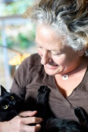 Caroline Bobby holding a black cat in her arms